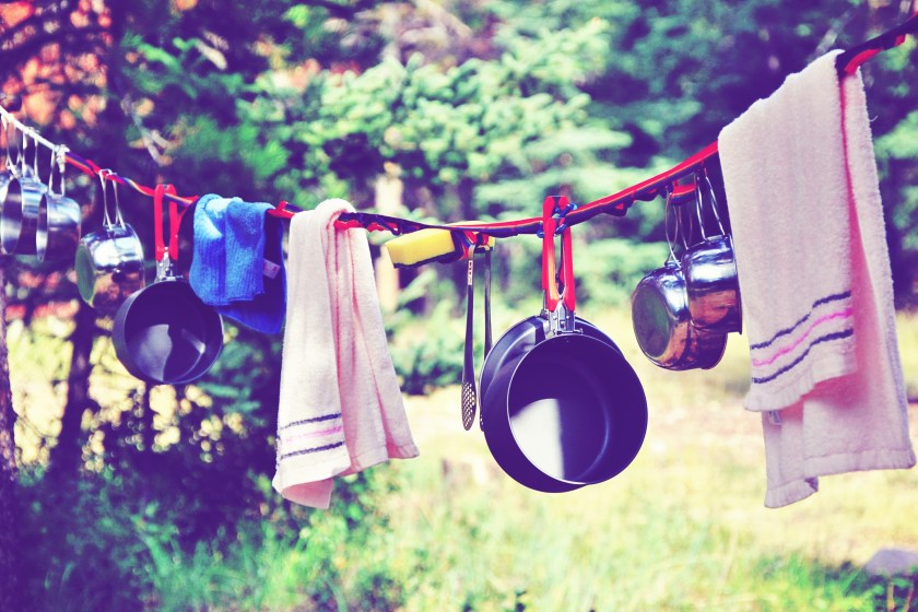 camping towels and pots hanging on a drying line