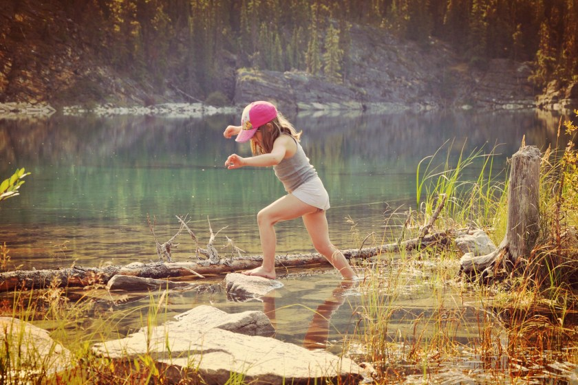 a young girl barefooted hoping across rocks in a lake