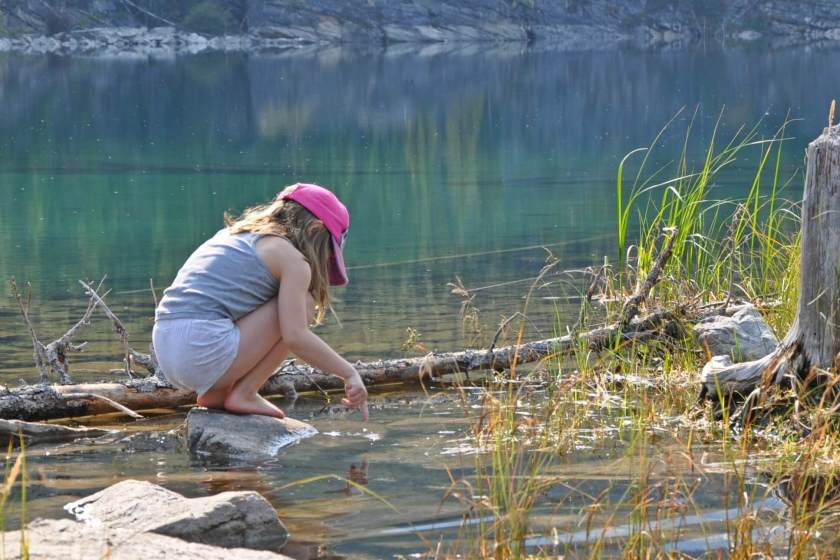 young girl playing in the water at the edge of a rocky lake, at Horseshoe Lake in Jasper National Park
