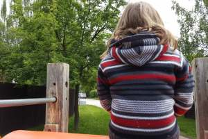 a young child wearing a black and red sweater is sitting a top a playground structure, looking away from the camera