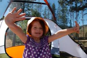 young girl waving her arms wide with a tent in the background