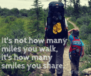 A child and adult hiking through the woods, text reads it's not how many miles you walk, it's how many smiles you share