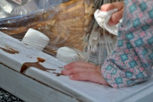 baby hands pressing down on a pizza box solar oven