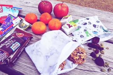various hiking snacks laid out on a wooden table
