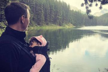 Dad exploring nature with his baby. He is looking out over a mountain lake while baby sleeps in a front baby carrier