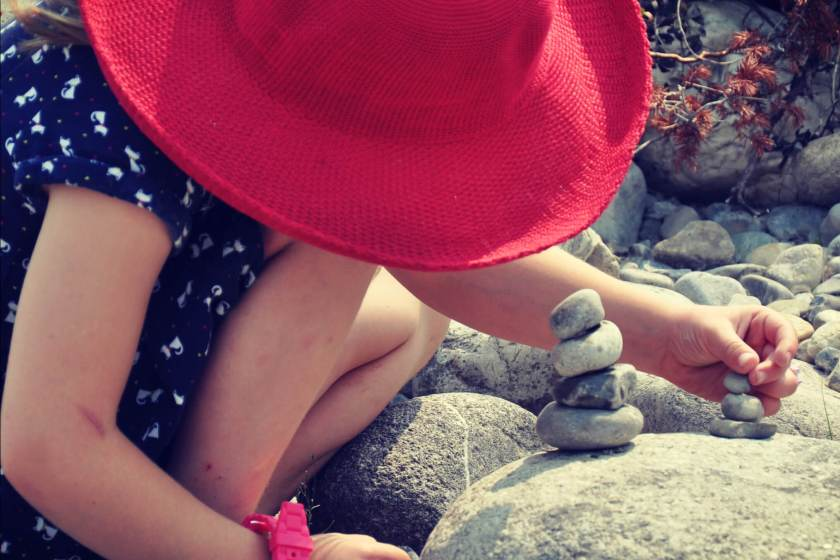 young girl wearing a large red sunhat being creative outdoors by building with stones on the shore