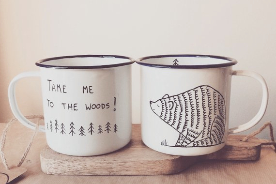 Two white enamel camping mugs on a wooden table. One mug reads take me to the woods. The other is an illustration of a bear.