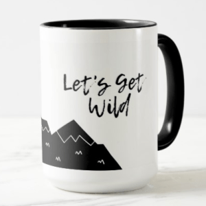 A white mug with black mountains and the words Let's Get Wild in script