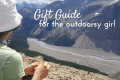 a woman looking out over a mountain valley, text reads gift guide for the outdoorsy girl