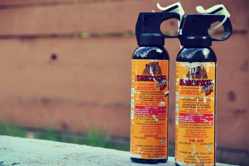 2 cans of bear spray sitting outdoors