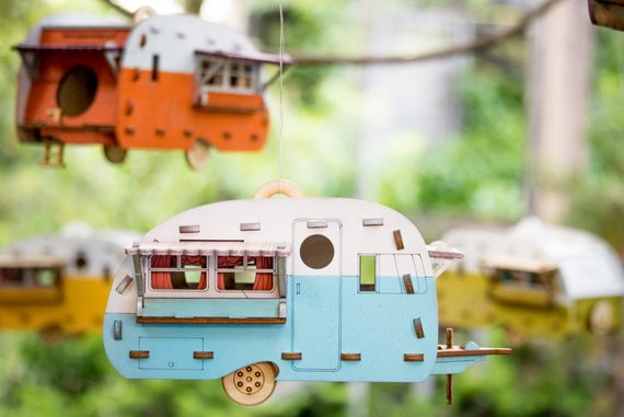 A cutout birdhouse camper hanging in a tree