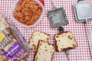 supplies to make campfire apple pies, bread, stewed apples, pie irons all on a red checkered picnic table