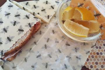 A sandwich and glass bowl waiting to be covered with beeswax wraps