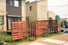 木製フェンスとデッキのある芝庭