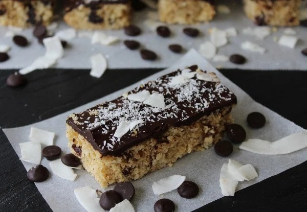 Chocolate Coconut Bars - packed with coconut, oats, & raisins topped with a dark chocolate coconut ganache. Made with coconut oil & naturally sweetened.