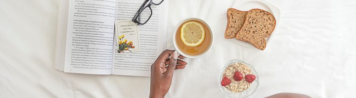 A birds-eye view of a black person's crossed legs as they sit in bed with breakfast and a book