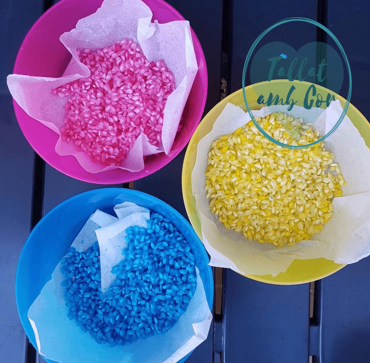 Resultado de teñir arroz: tres boles de colores rosa, azul y amarillo, con arroz en esos mismos colores