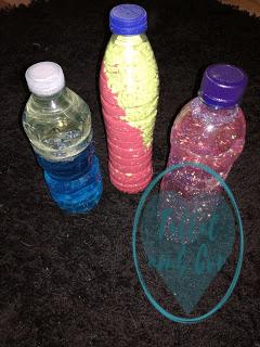 Tres botellas sensoriales sobre fondo negro: agua con colorante azul y aceite, piedras verdes y arena roja, agua con purpurina rosa y lila