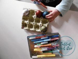 Manos de bebé de 2 años decorando con rotuladores unos huevos de Pascua pintados con pintura de dedos
