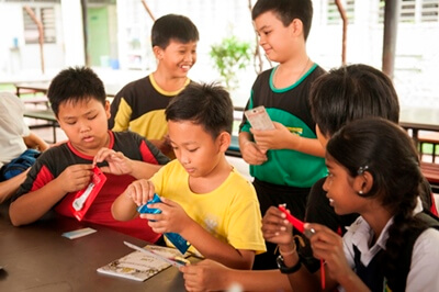 Kids at SK La Salle Jinjang excitedly unwrapping their gifts with their friends