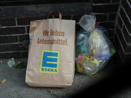 Foto mit einer Papier-Einkaufstüte am Müll, Aufdruck auf der Tüte ist Wir lieben Lebensmittel.