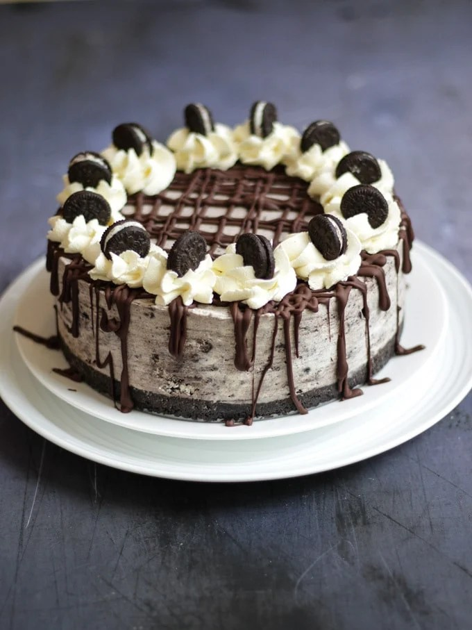 Side angle photo of a no bake Oreo cheesecake on two white plates. Drizzled with dark chocolate, topped with piped whipped cream and topped with mini Oreos and a pack of Oreo cookies in the background on dark grey background.
