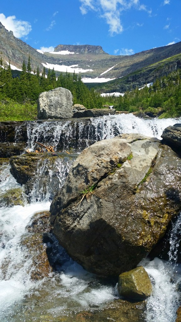 Waterfall with large rocks at Glacier National Park