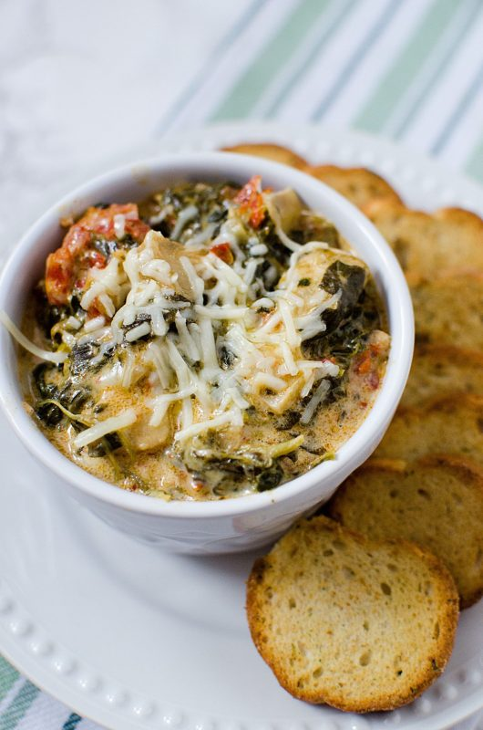 Slow Cooker Crock Pot Spinach Artichoke Dip with sun-dried tomatoes and artichokes. Perfect for holiday parties, football super bowl parties and more! So easy to make