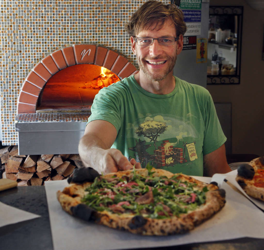Hombre sirviendo una pizza agradable, crujiente delante de un horno de pizza de leña grande