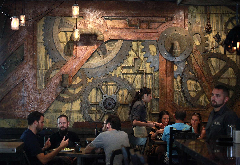 Diners en mesas delante de una pared decorada con engranajes industriales y tuberías