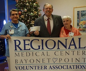 Rev. Jack Long (center), chaplain of Regional Medical Center Bayonet Point, accepts $2,000 check from Elliot Lorenzi, president of the Volunteer Association, and Shirley Dunn, the association's treasurer.