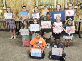 Children pose with their signed artwork.