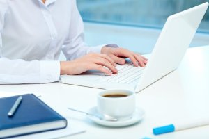 Woman on a laptop with a book and cup of coffee next to her.