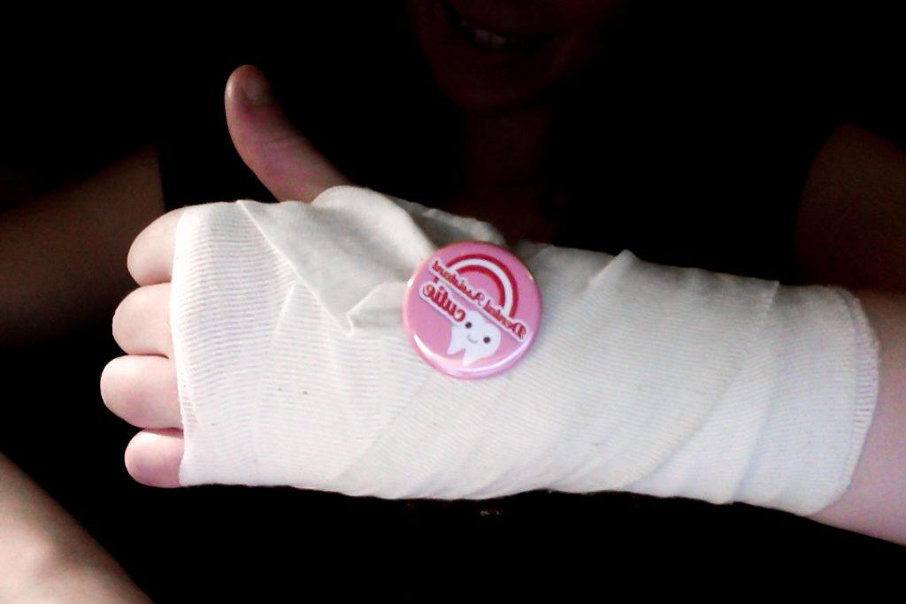 Bandagerad hand med tummen upp.