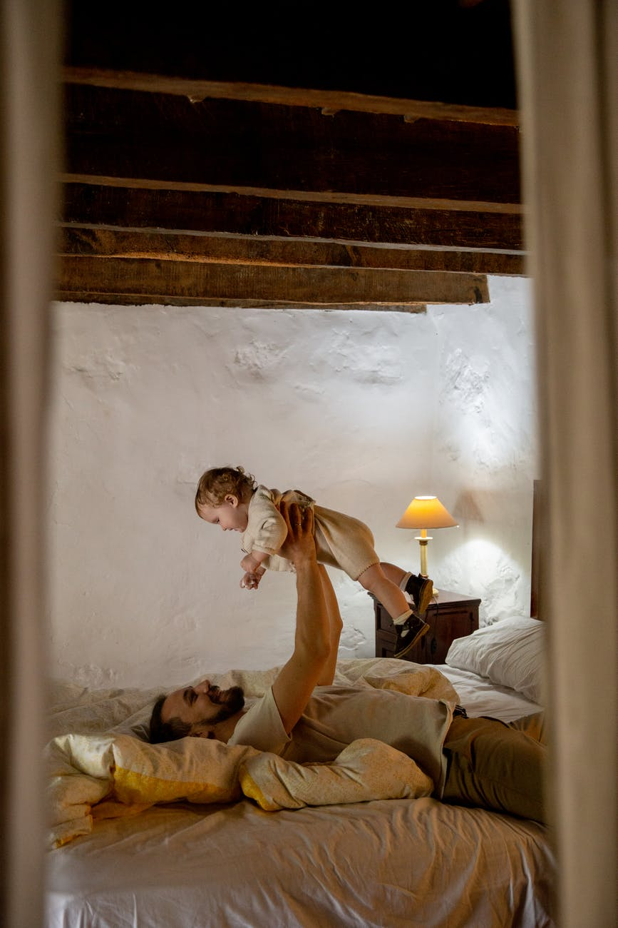 smiling bearded man with cute toddler kid lying on bed in rural interior house