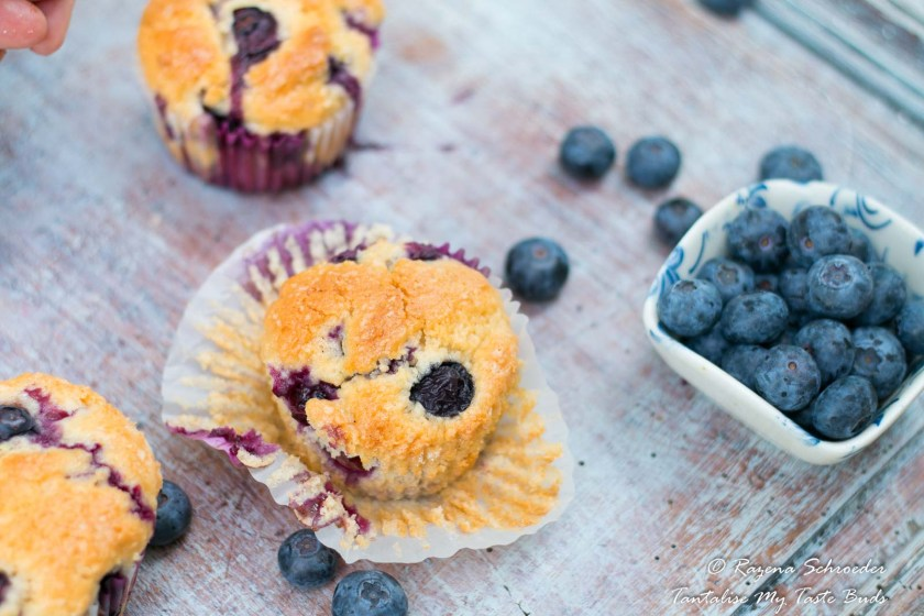 Moist blueberry muffins and fresh blueberries on wooden background
