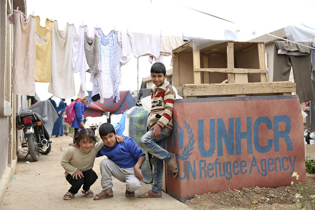 Three children are playing near one of the housing units.