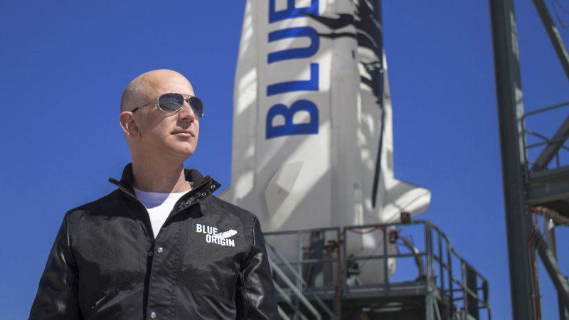 Jeff Bezos in sunglasses standing in front of Blue Origin's New Shepard rocket