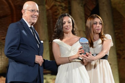 La vincitrice del Contemporary Fashion Maria Sapia premiata dal presidente onorario della Camera Nazionale della Moda Italiana e di Taomoda, cav.Mario Boselli, e da Adriana Santonocito di OrangeFiber