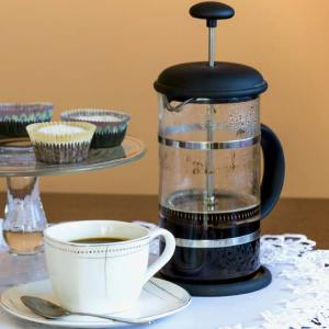 A partially filled French press sits besie a fille coffee cup with a spoon in the saucer. A tray of pastries is beside the coffee service.