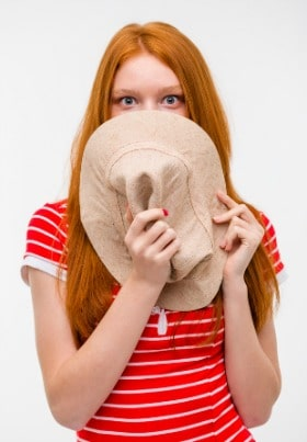 Woman hiding behind hat feeling too shy to stand out