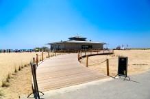 Eine schöne Strandbar mit Himmelbetten im Sand bei Tag