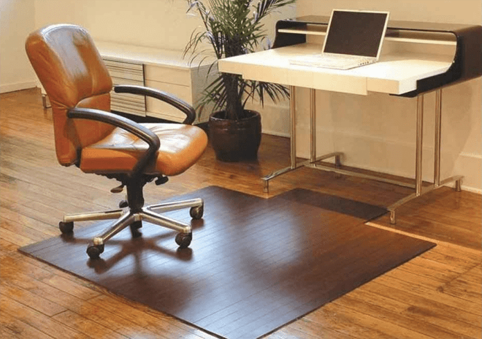 An image of a computer chair on top of a floor mat.