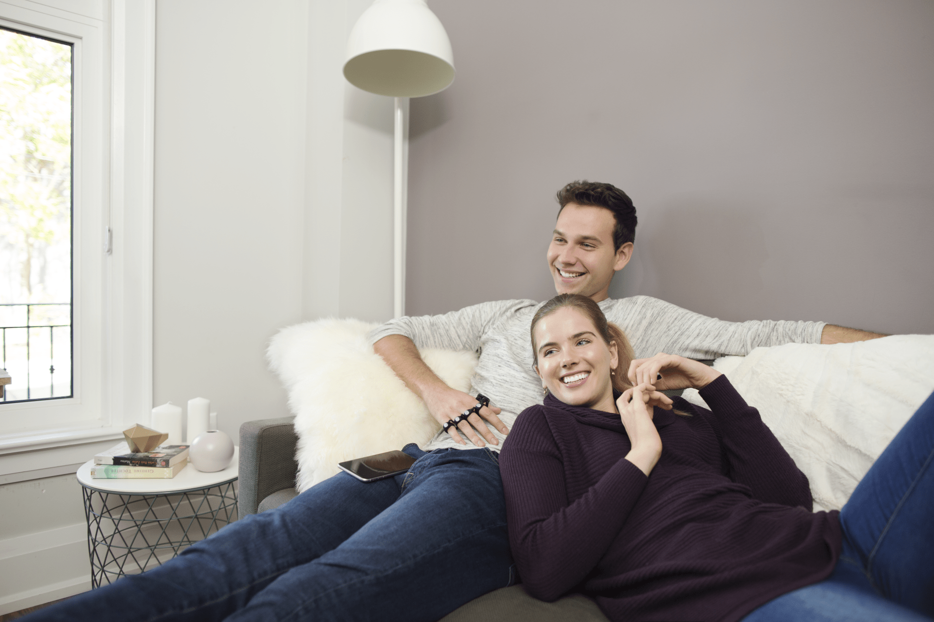 A couple lays on the couch and controls their smart TV using the Tap wearable