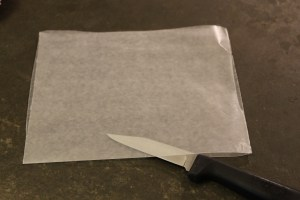 Fold the wax paper lengthwise, making sure the straight edges match. Using a very shark paring knife (this works best), cut along the fold.