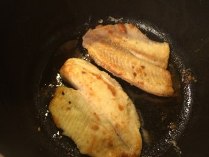 Browning the fish. The flour coating helps to hold the fish together during cooking.