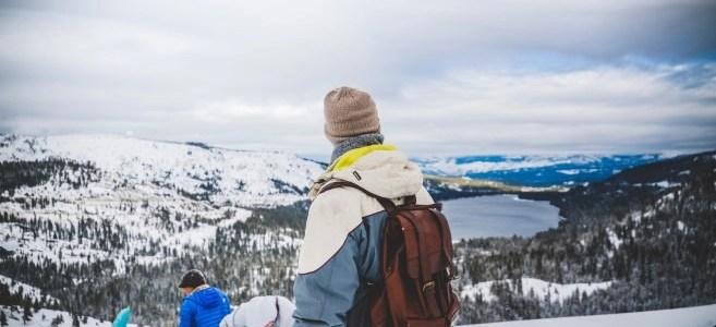 Mann mit Lederrucksack auf schneebedeckten Berg