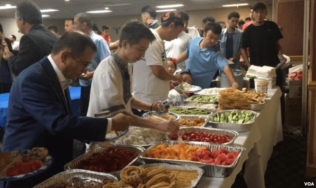 Uighurs eat breakfast together following an Eid prayer at an event in Falls Church, Virginia, Aug. 21, 2018. (B. Gallo/VOA)