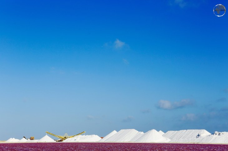 The purple briny water of a salt-water pond contrasts against the mounds of white salt at the Cargill Salt Mine.