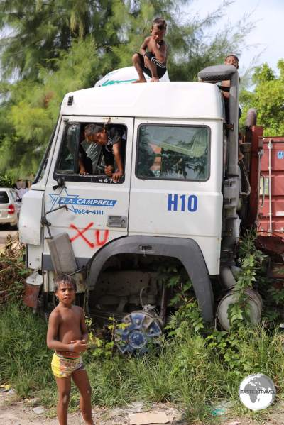 An abandoned truck on Betio island serves as a playground for local boys.